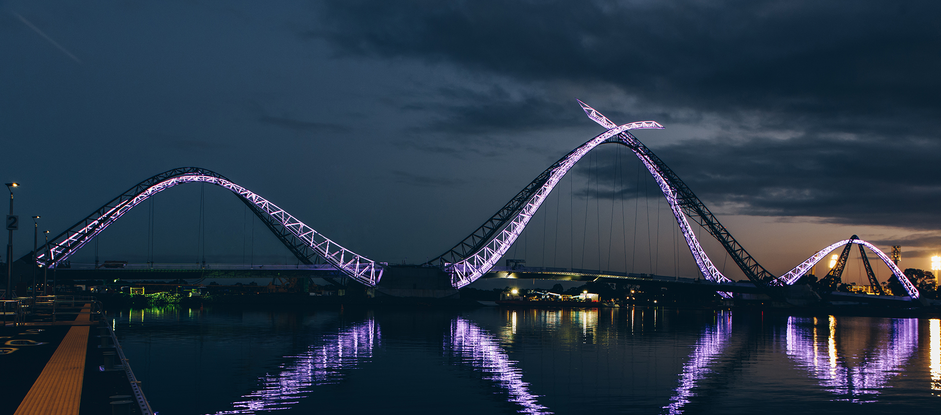 The Matagarup Bridge lit up in purple at night.